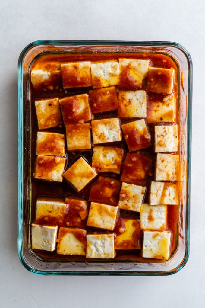 glass dish filled with tofu cubes that are covered in a dark colored marinade