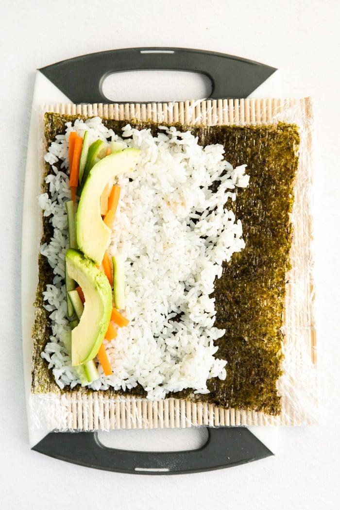 adding rice, avocado and cucumber to a nori sheet
