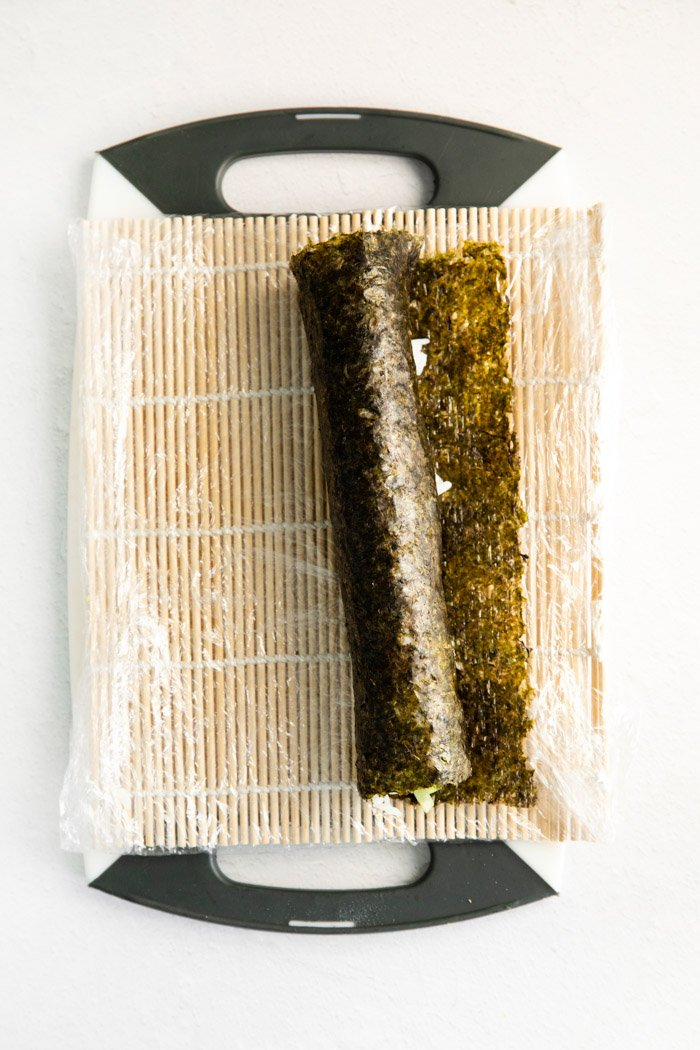 rolling up a nori sheet with filling