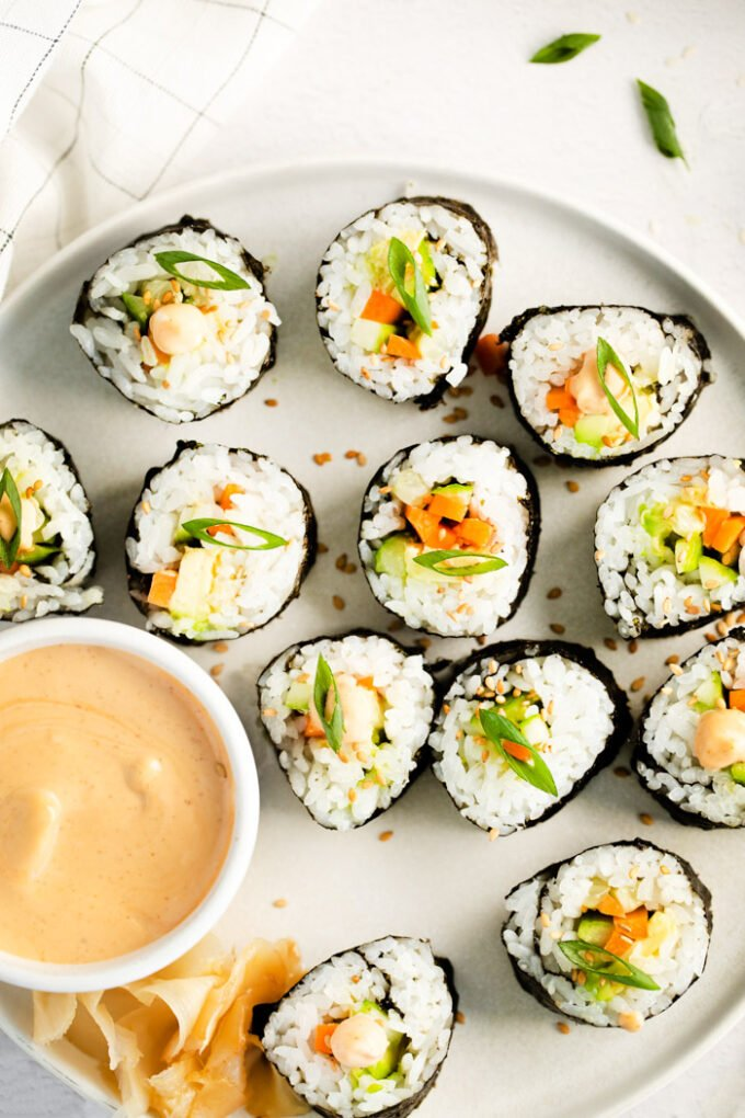 cucumber sushi rolls on a plate with dipping sauce