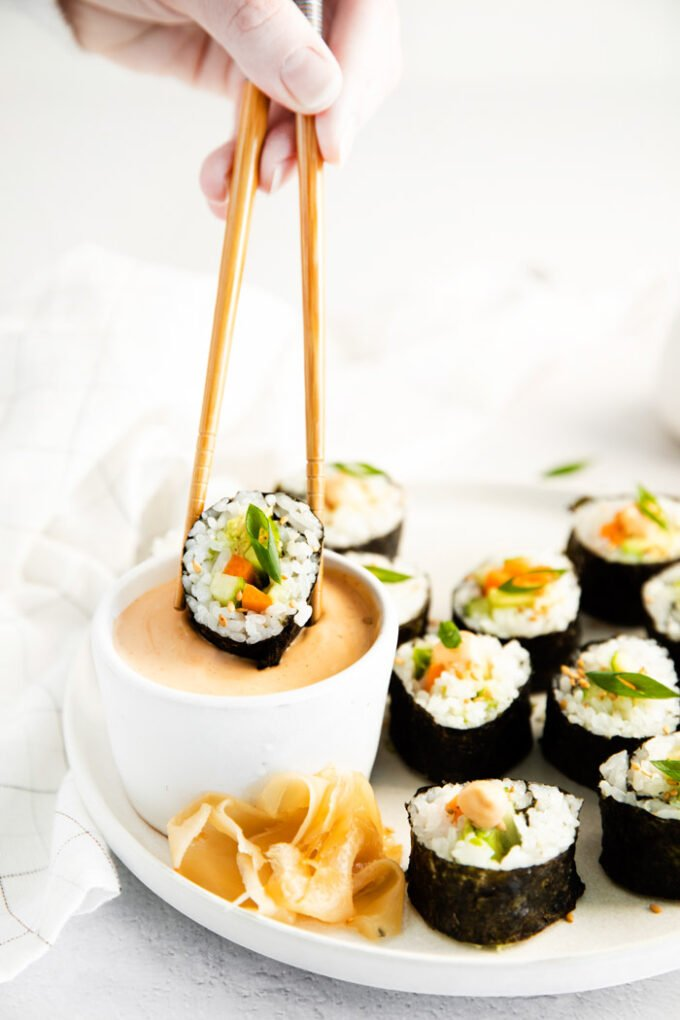 using chopsticks to dip a cucumber roll into spicy mayo