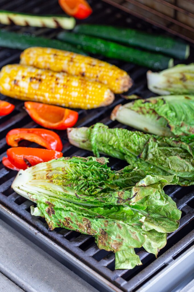 fresh veggies cooking on a grill including romaine lettuce, red bell pepper, corn, and zucchini