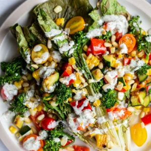 grilled romaine lettuce topped with mixed veggies and a white salad dressing