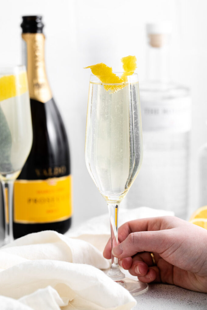 hand holding a French 75 Cocktail in a champagne flute