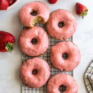 strawberry glazed donuts on a wire cooling rack with fresh strawberries around