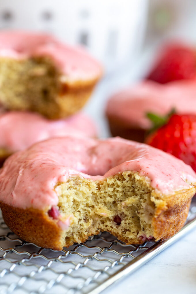 baked donuts topped with a pink strawberry glaze. big bite take out of the front donut