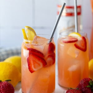 glass filled with strawberry lemonade vodka with a bottle of vodka in the background and garnished with fresh lemon and strawberries