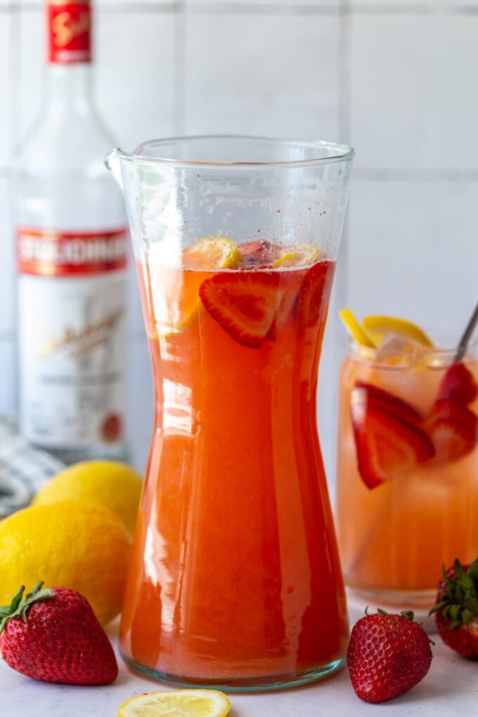 strawberry vodka lemonade in a tall pitcher with fresh fruit around and a bottle of vodka in the background