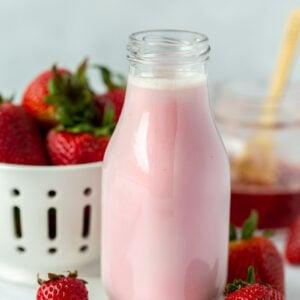 Strawberry milk in a glass milk jar