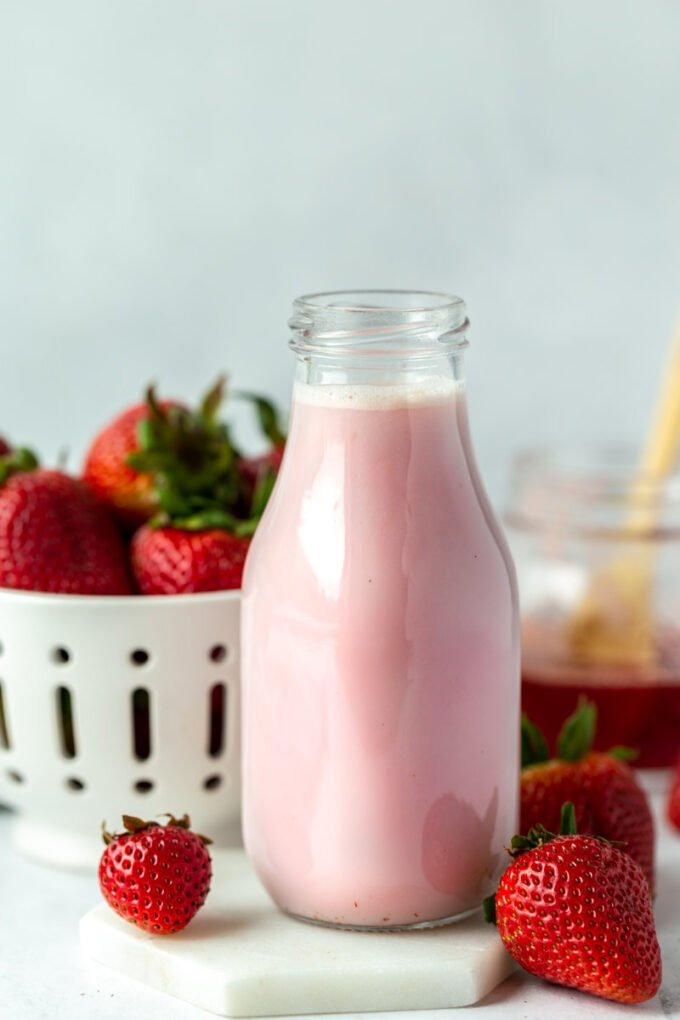 homemade strawberry milk in a glass jar with fresh strawberries