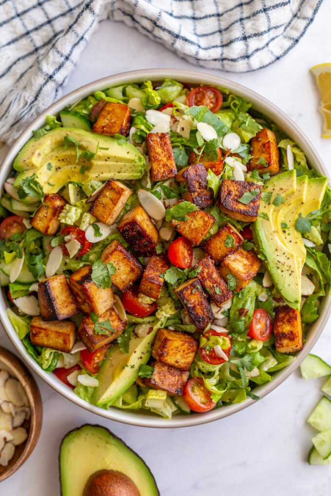 tofu salad topped with sliced avocado and cherry tomatoes