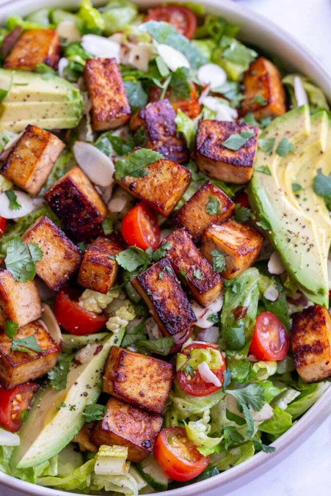 salad topped with marinated tofu, avocado and cherry tomatoes