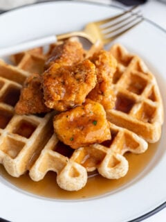 waffle on a white plate topped with vegan chicken nuggets