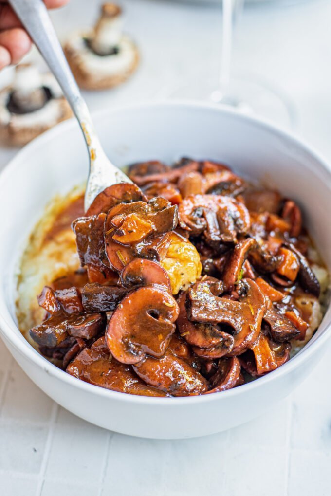 fork in a bowl of mushrooms bourguignon served over mashed potatoes