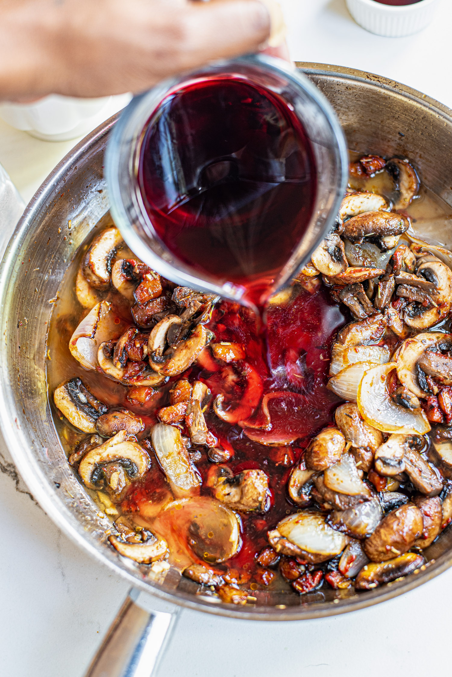 pouring red wine over mushrooms in a skillet