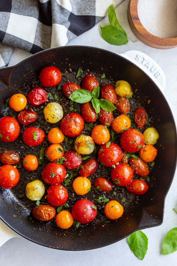 cast iron skillet filled with blistered tomatoes