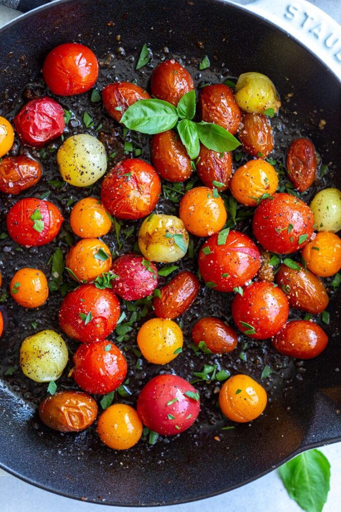 cherry tomatoes sautéing in a cast iron skillet