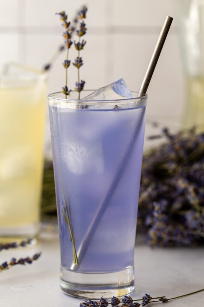 purple lavender lemonade in a tall glass with fresh lavender and a straw in it
