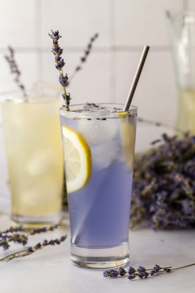 lavender lemonade in a glass with a slice of lemon and a sprig of lavender