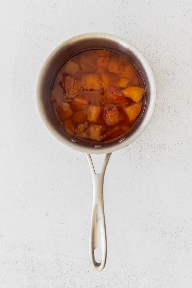 making peach simple syrup in a small pot