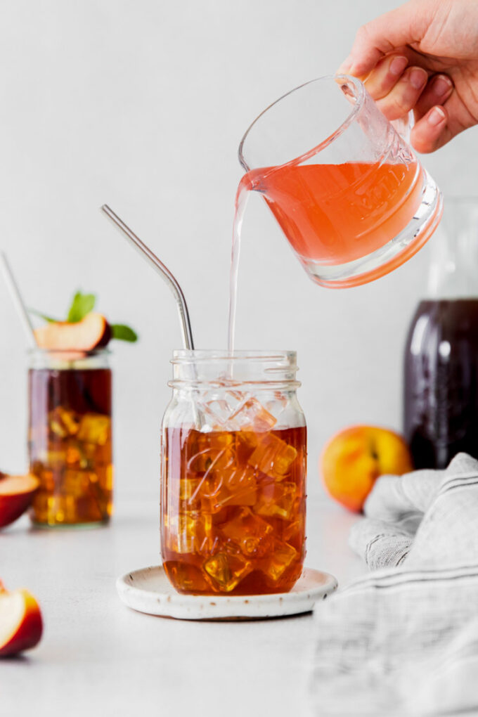 pouring peach simple syrup into a glass filled with ice and tea