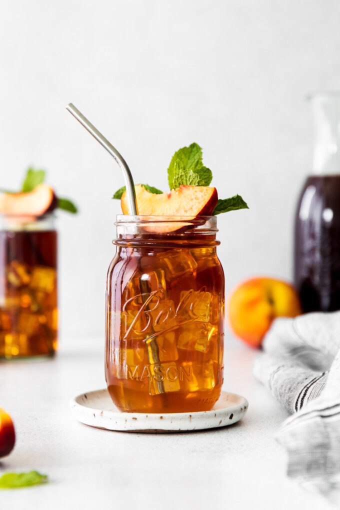 tall glass of peach iced tea garnished with fresh peach slice and mint