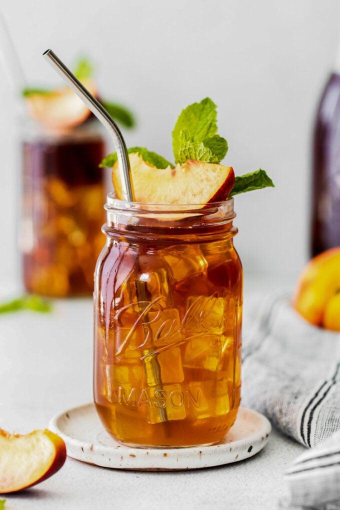 peach iced tea served in a mason jar with a peach slice