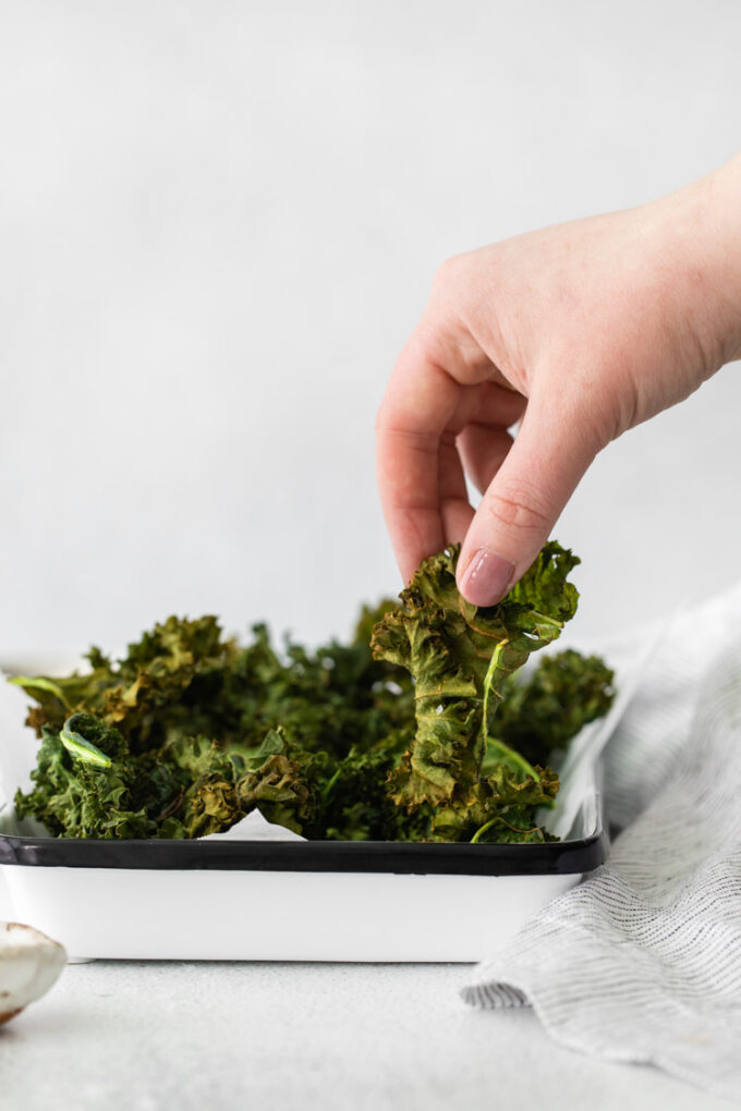 hand grabbing air fryer kale chips off of a serving plate