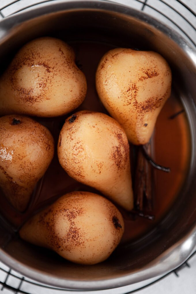 pears cooked in flavored syrup in a large pot