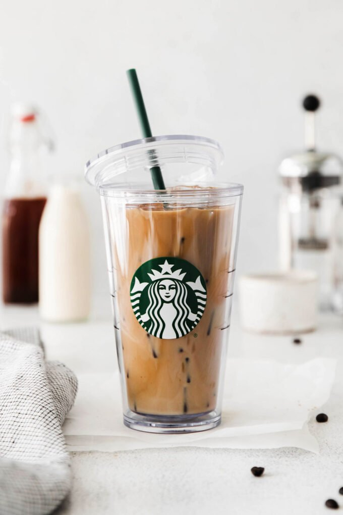 ice brown sugar latte in a starbucks cup with the lid hanging off the side