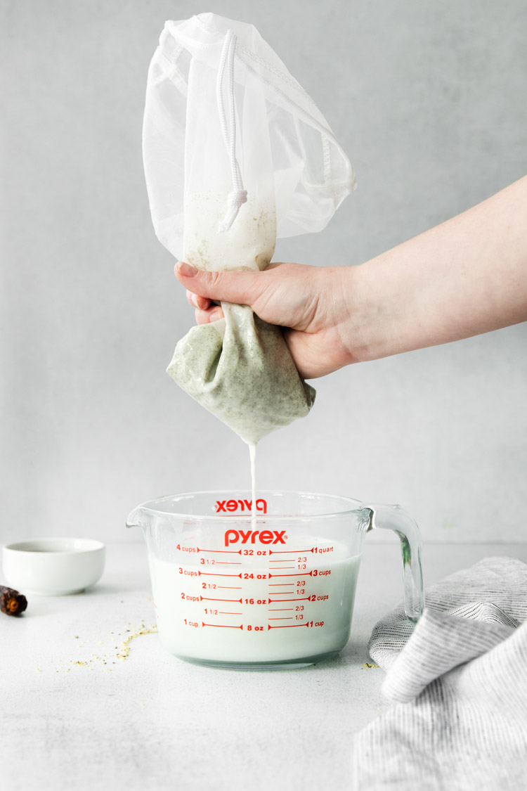 straining milk into a liquid measuring cup