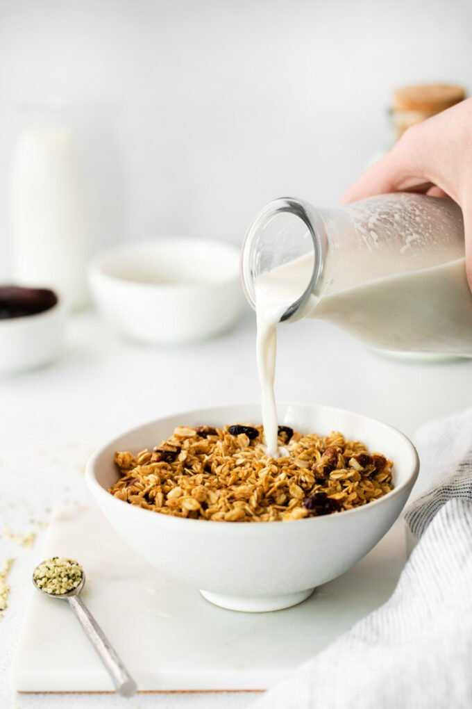 pouring hemp milk into a bowl of cereal