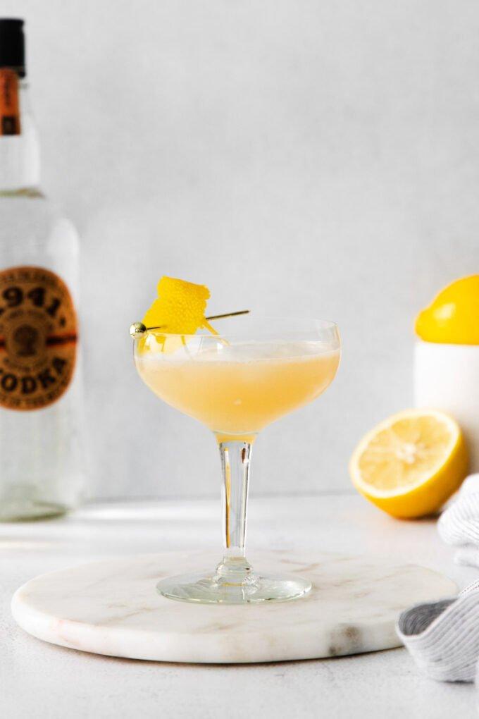 vodka sour cocktail served in a coupe glass with a garnish of lemon