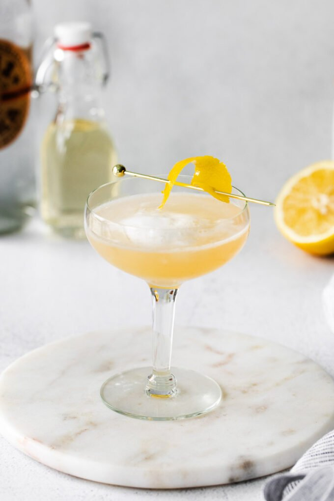 vodka sour drink in a coupe glass with a twist of lemon