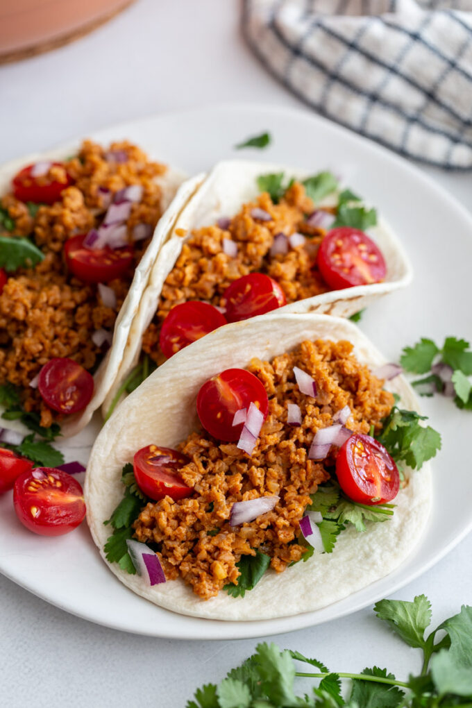 3 tacos on a plate topped with cilantro, tvp taco meat, cherry tomatoes, and onion