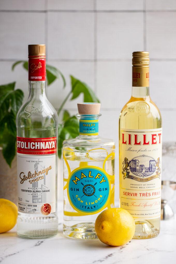 vesper martini ingredients: vodka bottle, gin bottle, and lillet bottle