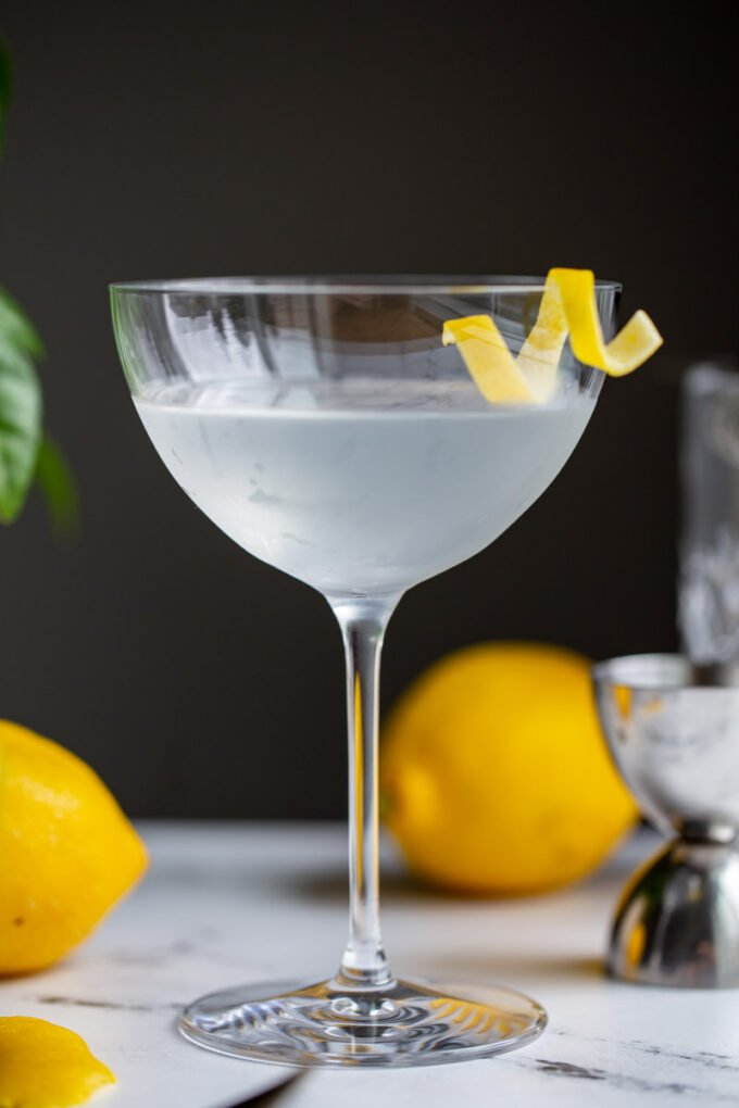 vesper cocktail in a cocktail glass with a lemon twist on the side
