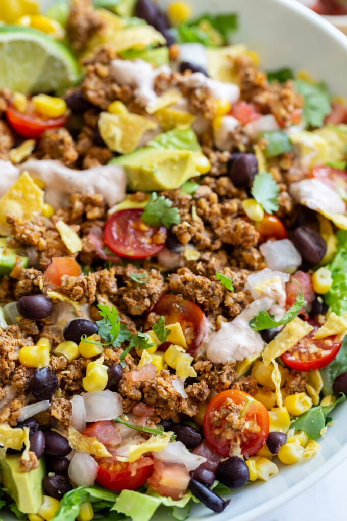 vegetarian taco salad loaded with lettuce, tomato, avocado, walnut meat, and a cream sauce