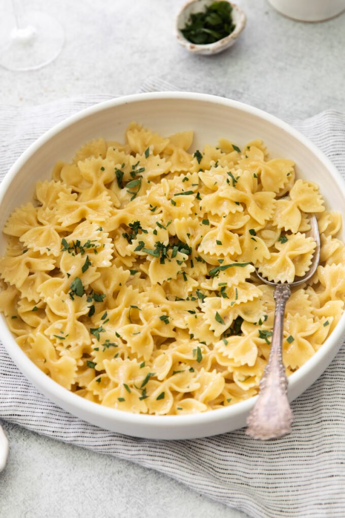large white bowl filled with bowtie pasta in a white wine sauce