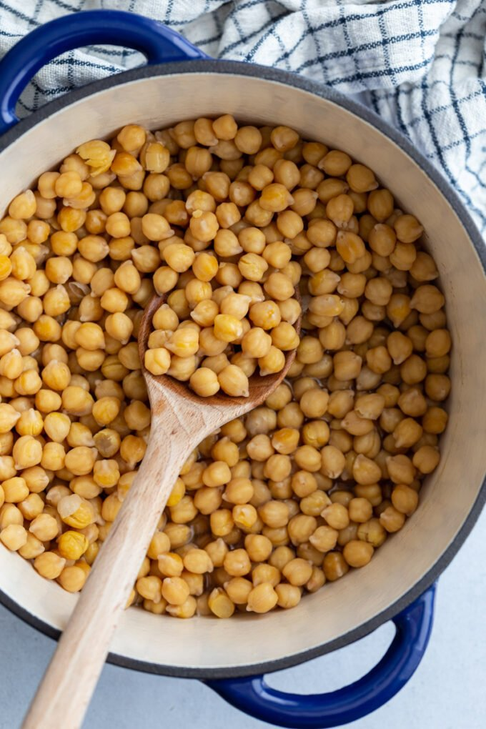 big pot of cooked chickpeas with a wooden spoon on the side