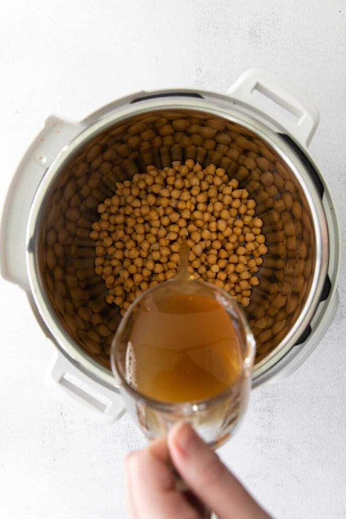 pouring vegetable broth in an Instant Pot with chickpeas