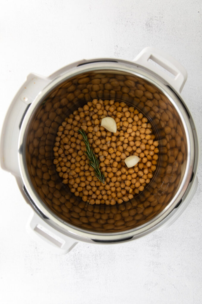 adding garlic and herbs to an Instant Pot with chickpeas