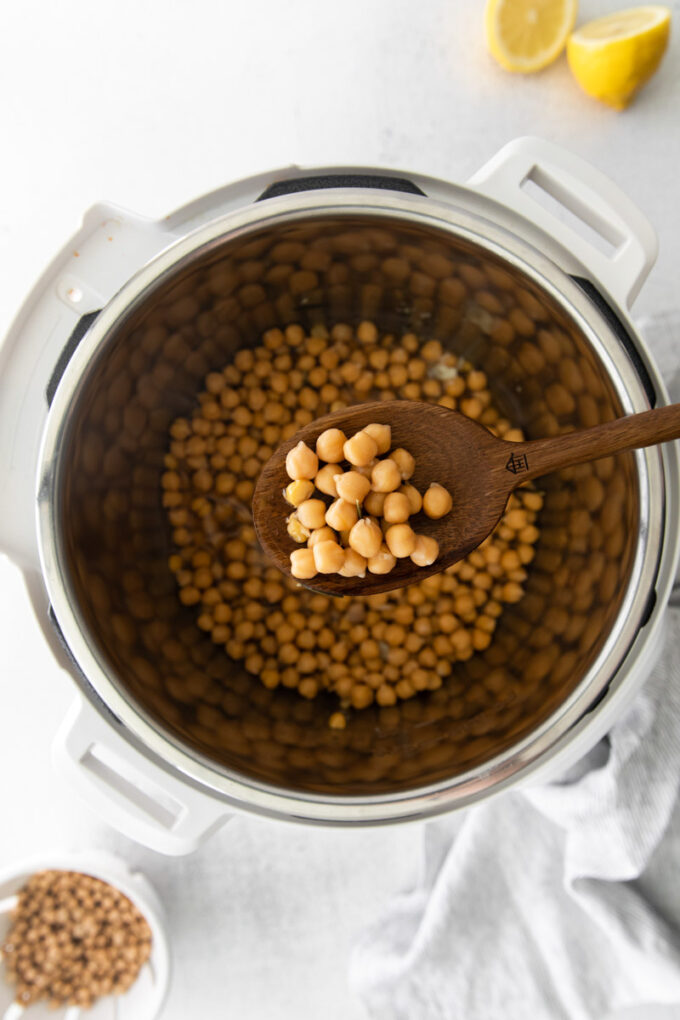 serving Instant Pot chickpeas with a wooden spoon