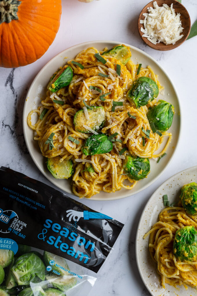creamy pumpkin pasta spaghetti on a plate with brussels on top and small pumpkins in the corner of the shot and a bag of ocean mist sprouts in the corner