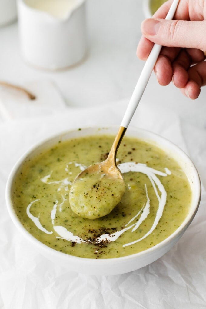 using a spoon to scoop up vegan zucchini soup out of a bowl