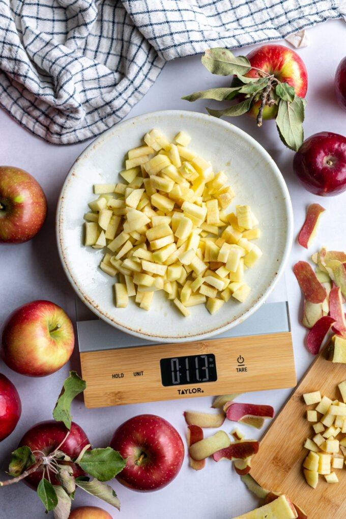 apple pieces on a plate on a kitchen scale with lots of apples and spple scrapes around the scene. towel in the corner and fresh apples around