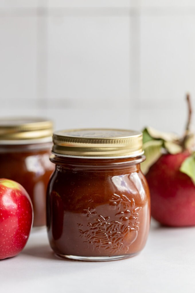 apple butter in a small jar with a golden lid and apples in the background