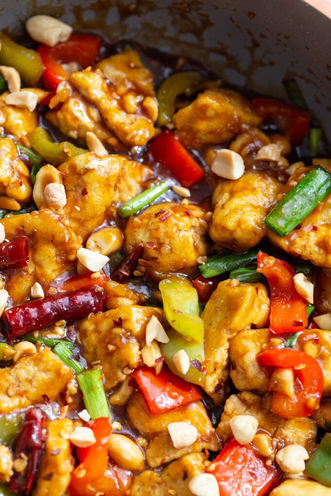 skillet of tofu, bell peppers and dried chilies in a sauce