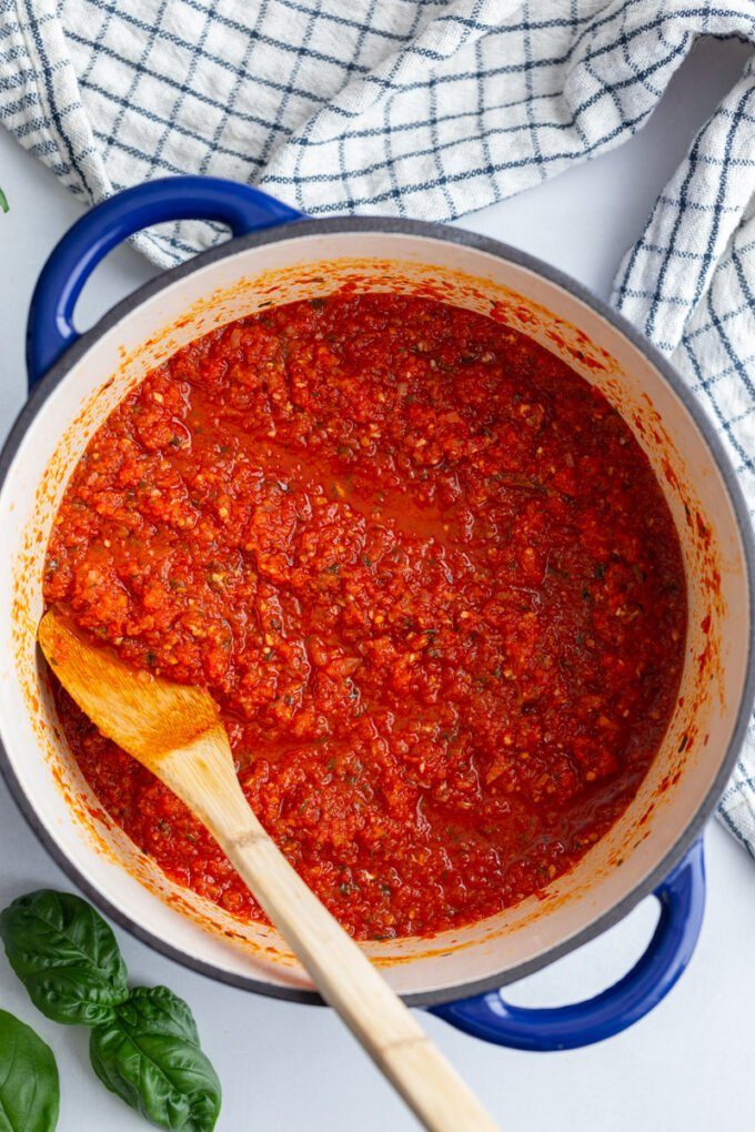 stirring pasta sauce with a wooden spoon