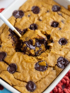 pumpkin baked oatmeal with chocolate chunks. A spoonful coming out of the middle of the dish